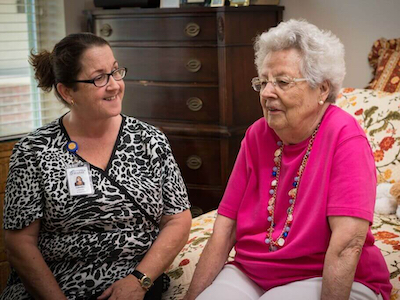 A volunteer woman and senior woman conversing in a bedroom.