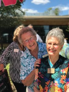 Two senior women at a social event smiling.